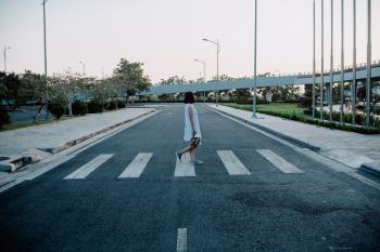 Woman Standing on Gray and White Road Crosswalk