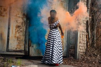 Woman Standing on Orange and Blue Smoke