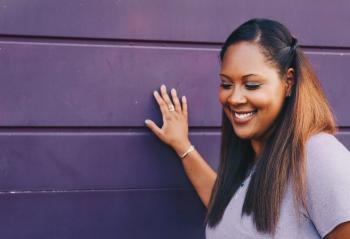 Woman Standing Touching Gray Wall Wearing Gray Shirt