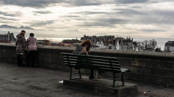 Woman Taking Photo While Sitting on the Bench Behind the Building Scenery