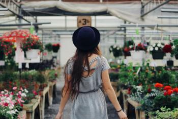 Woman Walking Between Display of Flowers and Plants