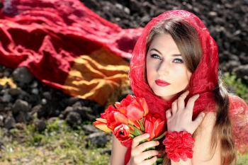 Woman Wearing a Red Scarf Holding Red Flowers