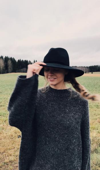 Woman Wearing and Holding Black Summer Hat Outdoor