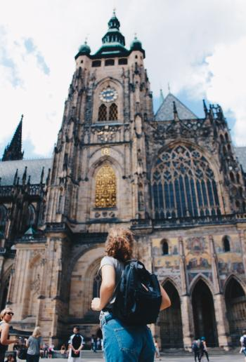Woman Wearing Backpack And Grey Shirt Near Brown Church