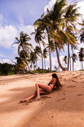 Woman Wearing Bikini Laying on Seashore