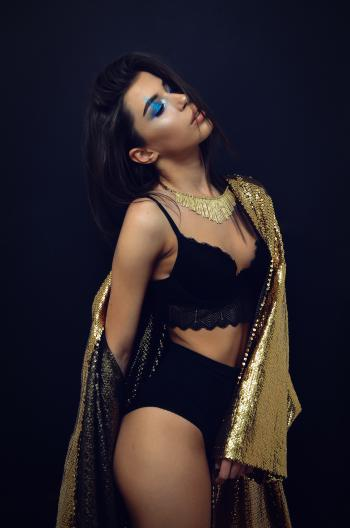Woman Wearing Black Brassiere and Panty With Sequinned Gold-colored Coat Robe