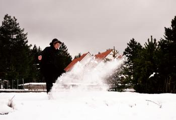 Woman Wearing Black Coat While Playing with Snow