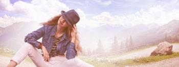 Woman Wearing Black Fedora Hat, Blue Denim Blazer and White Skinny Jeans While Sitting on Ground
