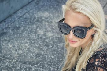 Woman Wearing Black Framed Wayfarer Style Sunglasses and Black Floral Top Near Gray Concrete Pavement