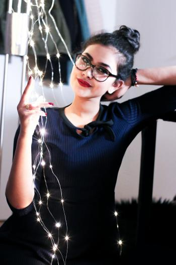Woman Wearing Black Knit Elbow-sleeved Top Touching Mini String Lights