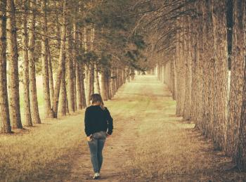 Woman Wearing Black Longsleeve and Gray Jeans Walking on Brown Forest