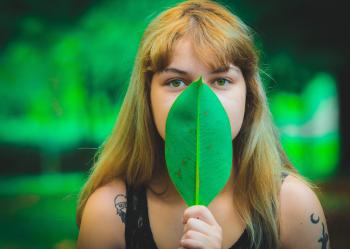 Woman Wearing Black Sleeveless Top Covering Mouth Using Green Leaf