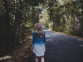 Woman Wearing Blue and White Long-sleeved Shirt Walking Near Tree