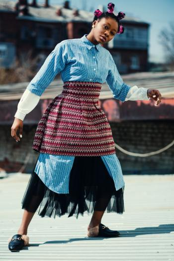 Woman Wearing Blue Long-sleeved Shirt and Red Skirt Standing on Roof