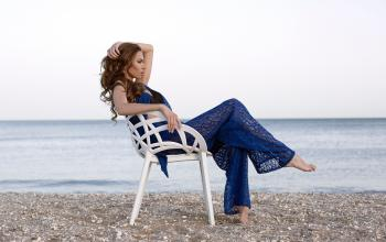 Woman Wearing Blue Two-piece Dress Sitting on White Armchair Near Beach