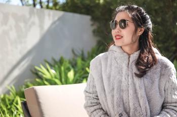 Woman Wearing Gray Fur Coat and Sunglasses Sitting Near Green Leaf Plants