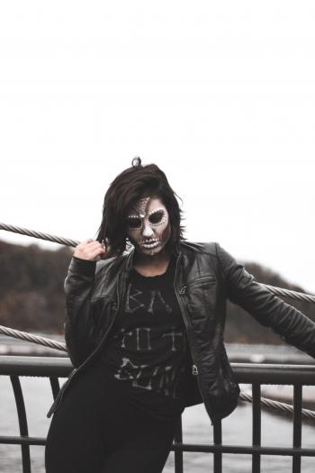 Woman Wearing Gray Halloween Mask and Black Leather Jacket Standing by Black Railings