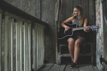 Woman Wearing Gray Tank Top Playing Black Cutaway Acoustic Guitar