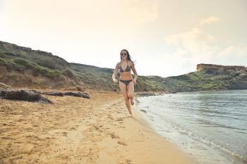 Woman Wearing Grey Bikini Running On White Sand Seashore