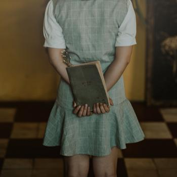 Woman Wearing Grey Dress Holding Book