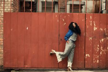 Woman Wearing Grey Jumpsuit Standing Beside Brown Metal Gate