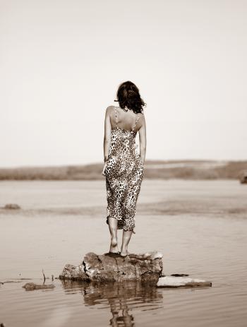 Woman Wearing Leopard Print Dress Standing on Stone on Body of Water