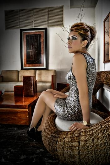 Woman Wearing Leopard Print Sleeveless Mini Dress Sitting on Wicker Brown Chair