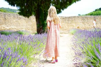 Woman Wearing Pink Maxi Dress Walking Along Unpaved Pathway With Purple Plants Nearby