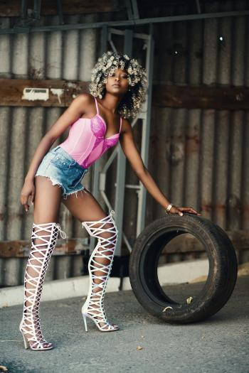 Woman Wearing Pink Spaghetti Strap Top and Blue Denim Shorts Holding Vehicle Tire