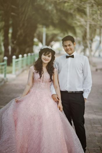 Woman Wearing Pink Wedding Gown Standing Next to Man Wearing White Dress Shirt