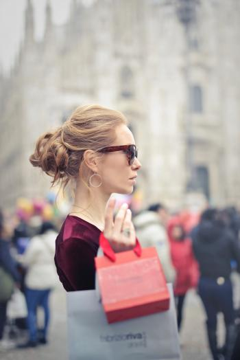 Woman Wearing Red Top Carrying Red Paper Tote Bag