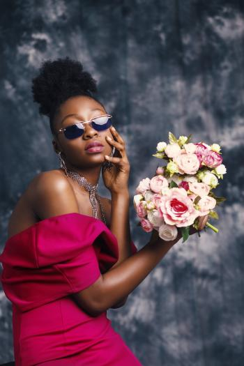 Woman Wearing Sunglasses and Posing for Pic With Flowers