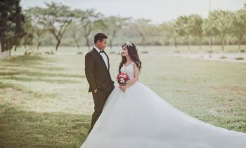 Woman Wearing Wedding Dress Standing Beside a Man Wearing Tuxedo