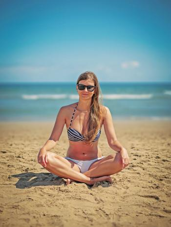 Woman Wearing White-and-black Bikini Sitting on Sand Near Seashore