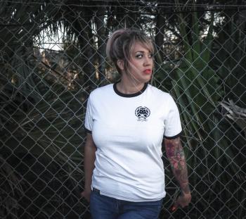 Woman Wearing White Crew-neck T-shirt With Black Trim and Blue Denim Bottoms Beside Wire Fence