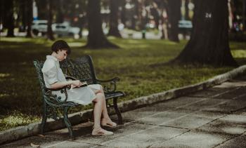 Woman Wearing White Dress Sitting on Bench