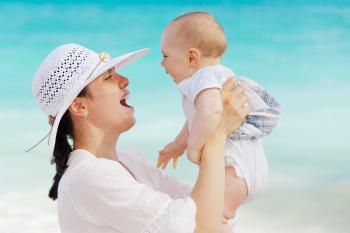 Woman Wearing White Hat Holding Baby Wearing White Onesie Near Beach during Day Time