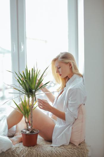 Woman Wearing White Long-sleeved Shirt Sitting Beside Green Plant