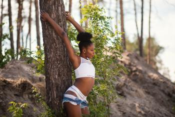 Woman Wearing White Sports Bra Holding Tree