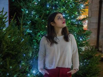 Woman Wearing White Sweater With Red Skirt Near Green Christmas Tree