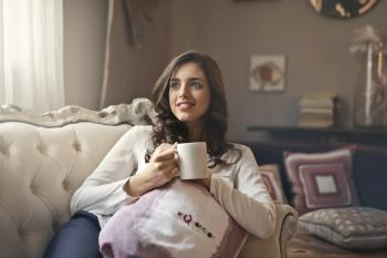 Woman Wearing White Top Drinking Beverage from White Ceramic Mug While Lying on Sofa Inside Well Lit Room