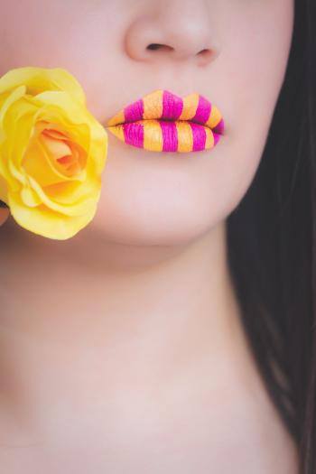 Woman Wearing Yellow and Pink Striped Lipstick Holding Yellow Rose