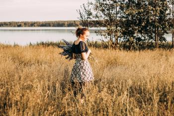 Woman Wears Black and Grey Dress Stands in Field