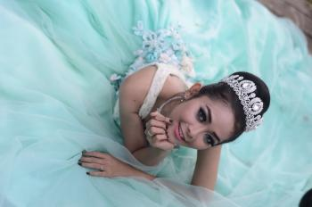 Woman Wears Teal Chiffon Gown and Crown