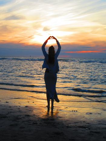 Woman With Arms Up Making Heart Sign While Standing on Beach at Sunset