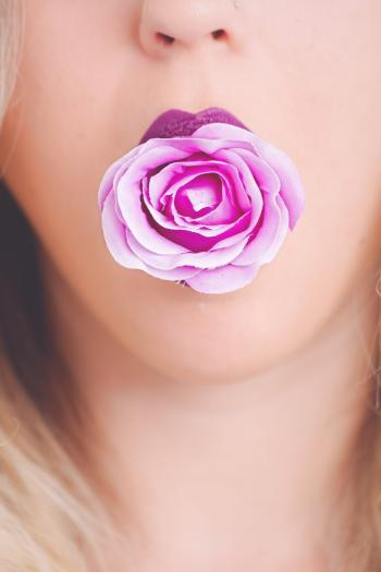 Woman with Pink Flower in the Mouth