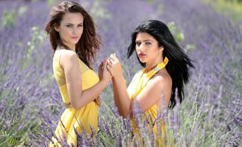Women in Yellow Dress Holding Hands in Purple Grassland