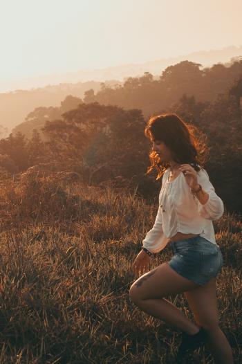 Women Wearing White Long-sleeved Blouse With Blue Denim Short Shorts Taken during Sunset