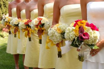 Women Wears White and Yellow Tube Strapless Dresses Holding White, Red, and Yellow Bouquet