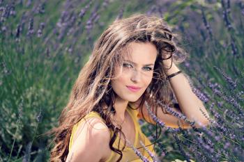 Women's Yellow Tank Top Holding Her Brown Curly Hair While Sitting on a Purple Flower